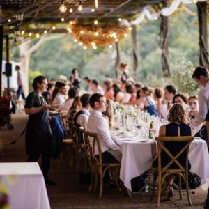 Guests Sitting At Long Dining Table At A Private Function, Sitting Underneath A Canopy.