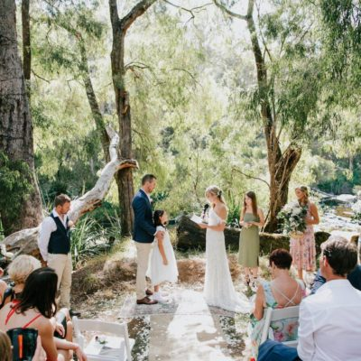 Wedding Ceremony Taking Place Next To A River In A Forest Area.