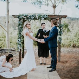 Wedding Ceremony Outside With A Bride, Groom, Celebrant And Bridesmaid Assisting With The Bride's Dress.