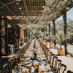 Long Table Set Up Ready For A Meal Underneath A Canopy.