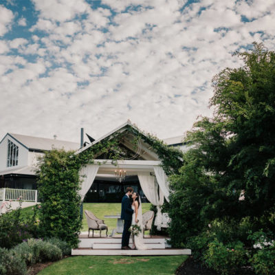 Bride and Groom in the Garden with Backdrop