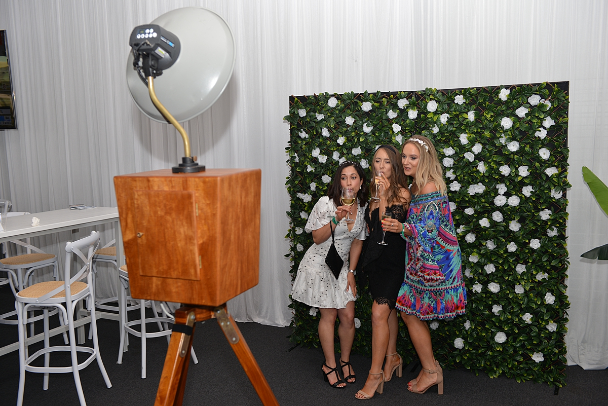 girls taking pictures at the photo booth
