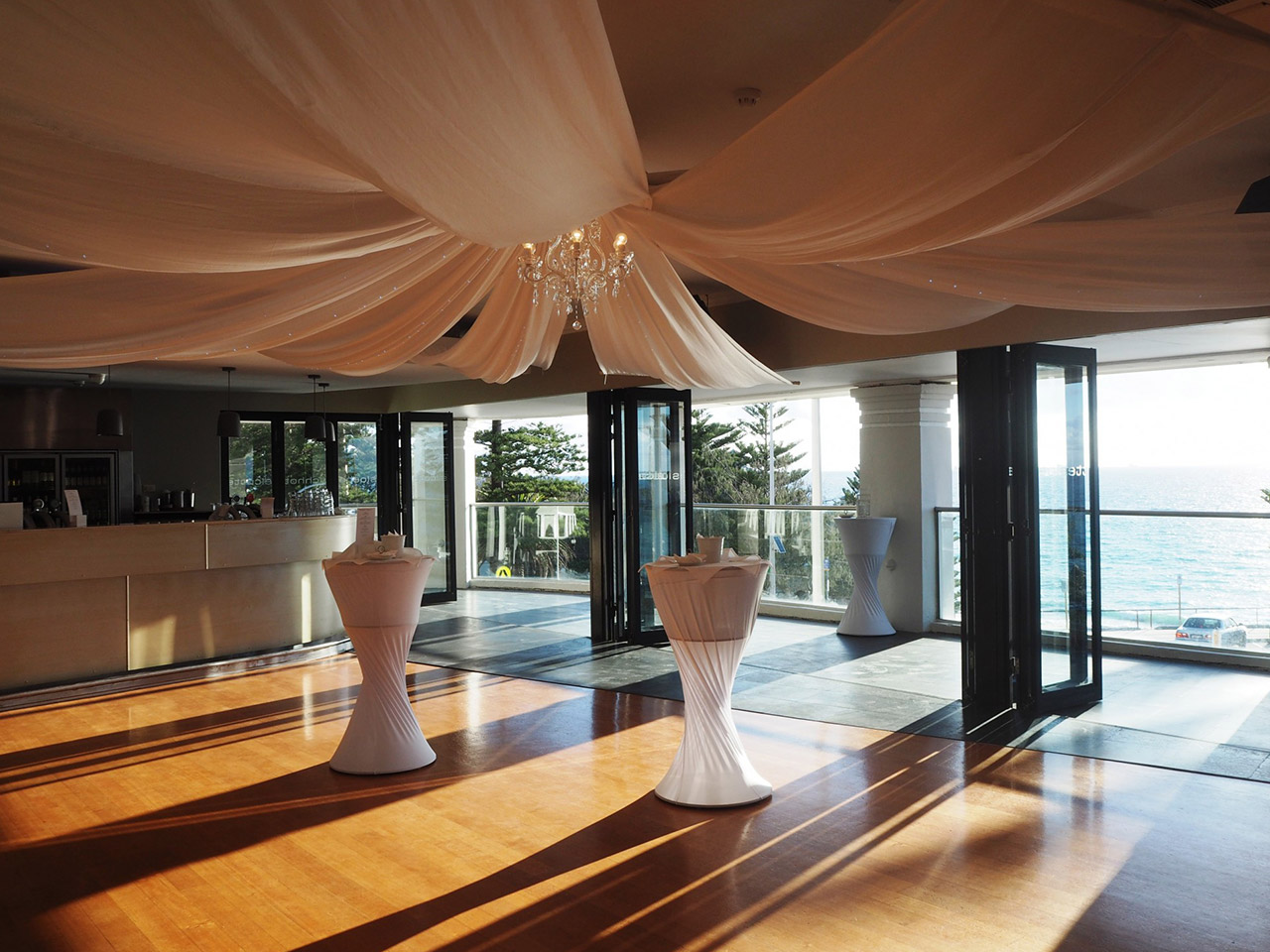 Inside The Function Room With Ceiling Curtains Draping And A Ocean View.