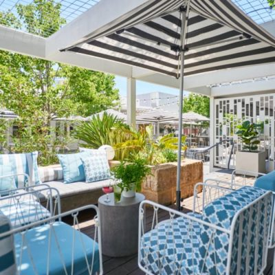 Chairs, Table And Umbrella Set Up On The Deck Area.