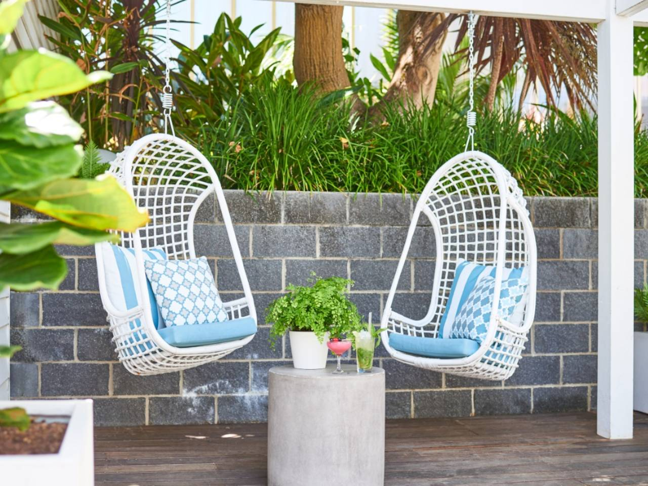 Two Hanging Chairs With A Small Table Set Up In The Private Functions Deck Area.