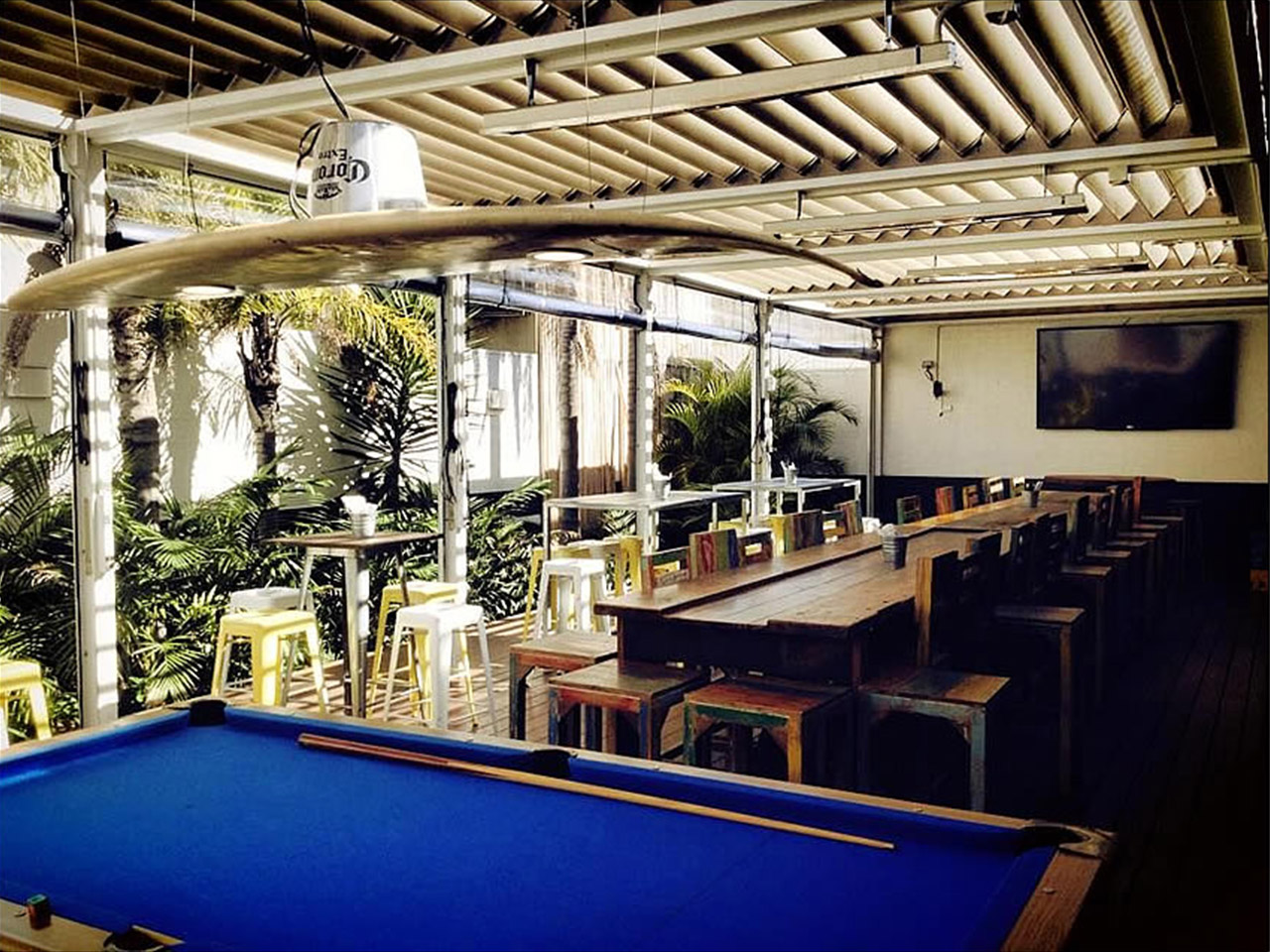 Long Table with chairs and a Billiard and a Surf Board in the Ceiling