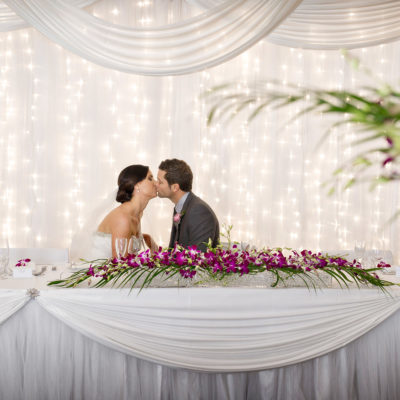 A Wedding Table With The Groom And Bride Sitting And Kissing.