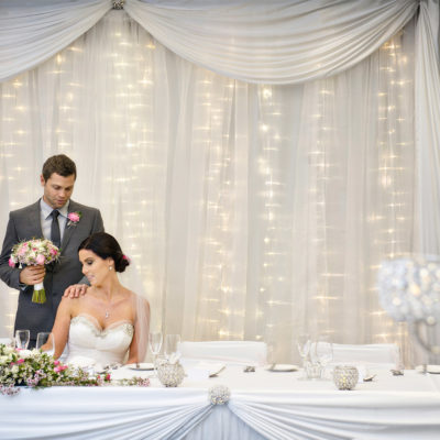 A Wedding Table With The Groom Standing Handing Over The Flower Bouquet To The Bride.