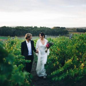 Bride And Groom Walking Down The Vineyard.