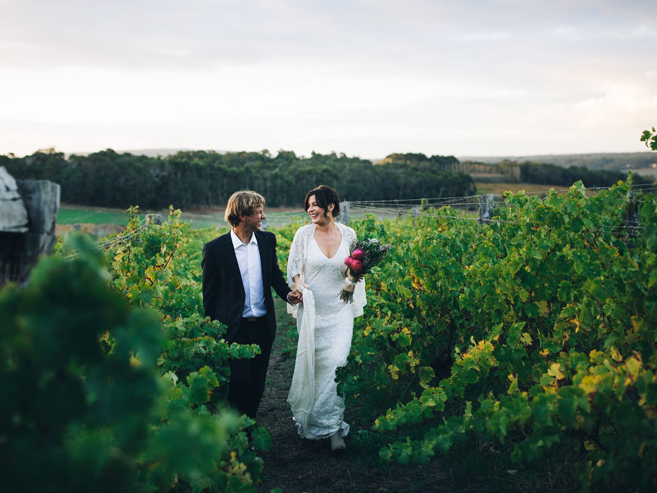 Bride And Groom Walking Down The Vineyard.