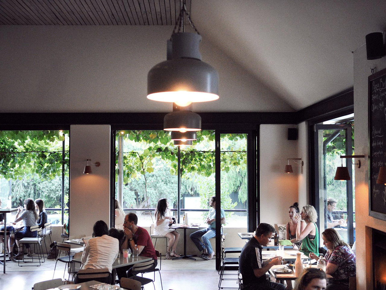 People Eating Inside the Restaurant With Hanging Lights.