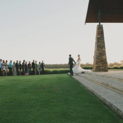 Bride and bridegroom walking across grass at venue