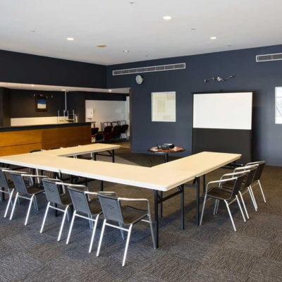 Function room where tables and chairs are set up in a U shape