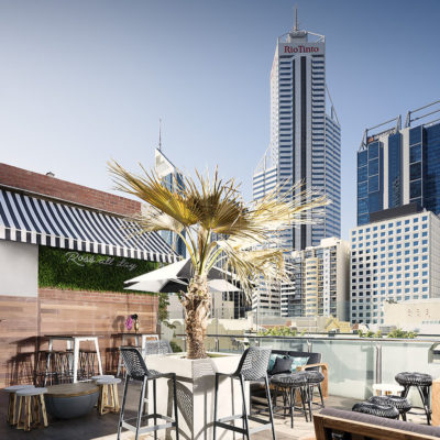 rooftop bar view of rio tinto building with palms