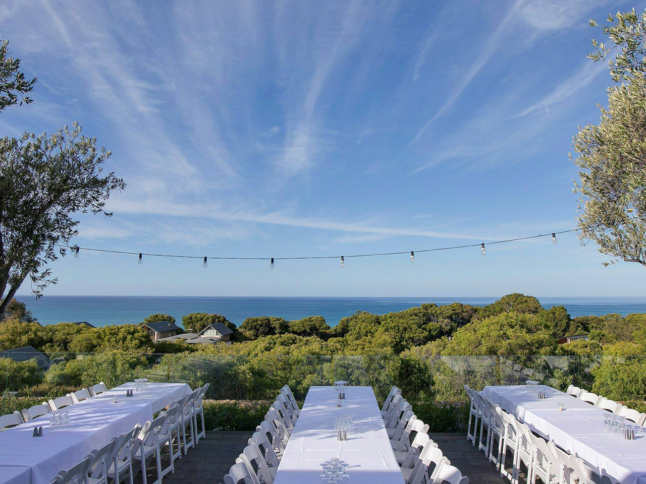 A Wedding Dinner Tables Set Up With The Ocean In The Background.
