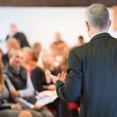 A Speaker In A Conference In Front Of The Guests