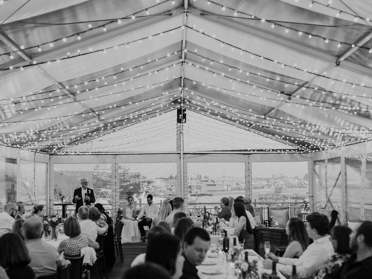 Black And White Capture of Wedding Reception Inside the Function Room With string Lights With Bride And Groom Sitting In Front , A Speaker And Guests