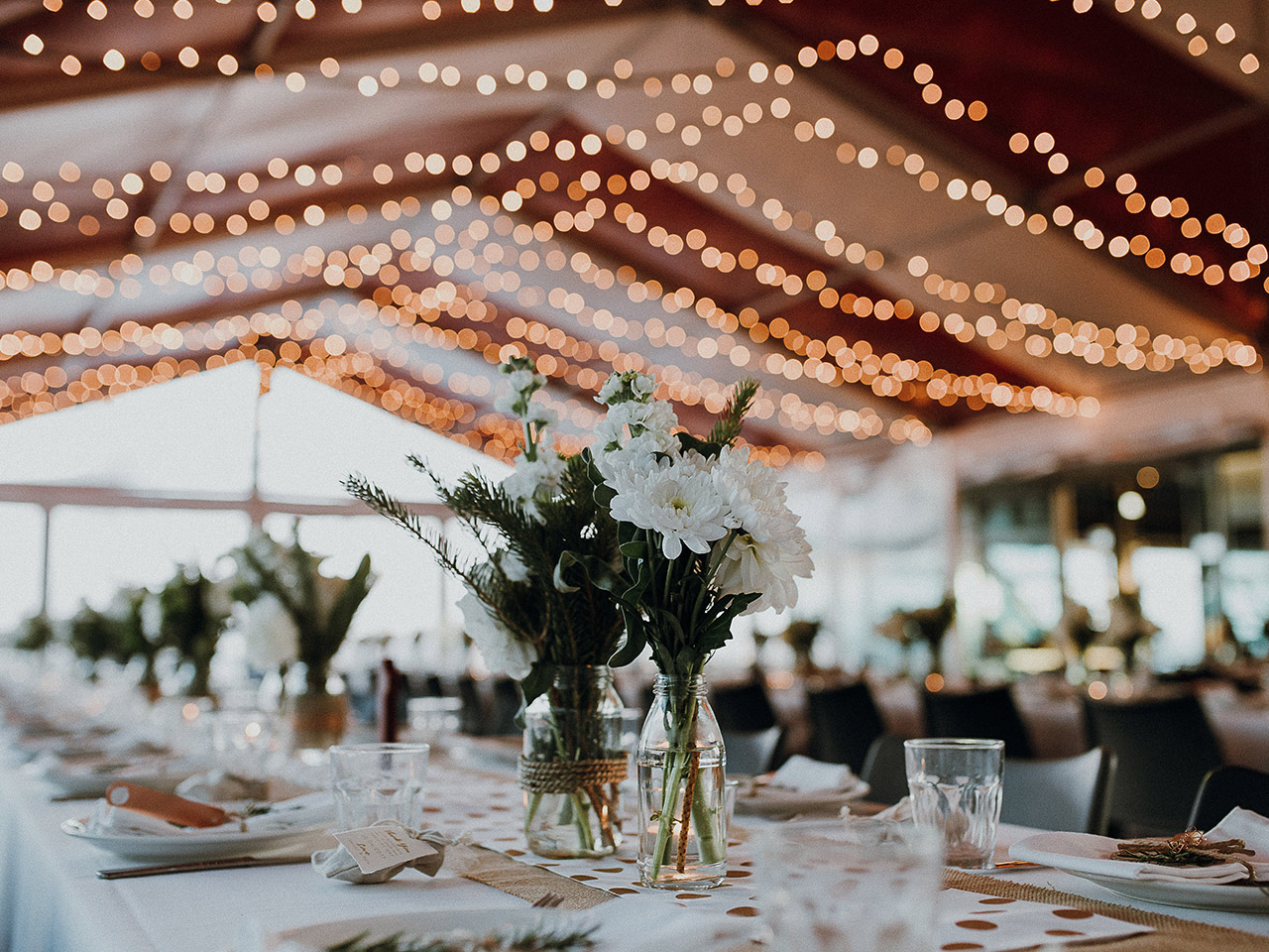 Inside the Function Room with Flower Centerpieces in Long Tables, String Lights and Drapings on the Ceiling