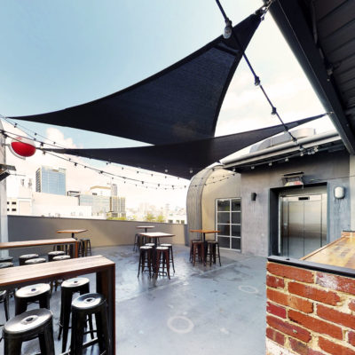 rooftop bar overlooking perth with tables and shade sails