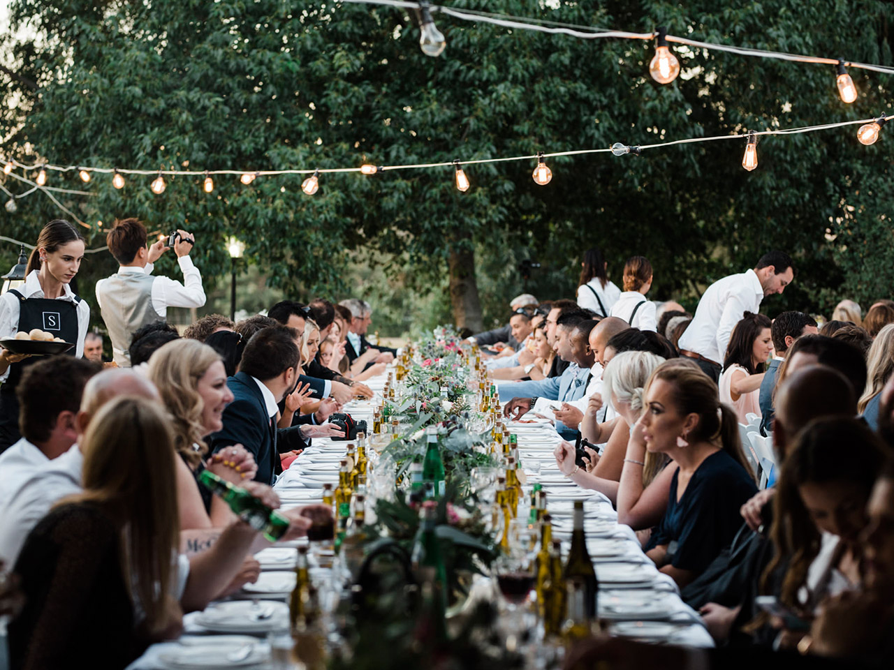 People Gathered In A Long Table With Food And Drinks And A String Lights In The Terrace