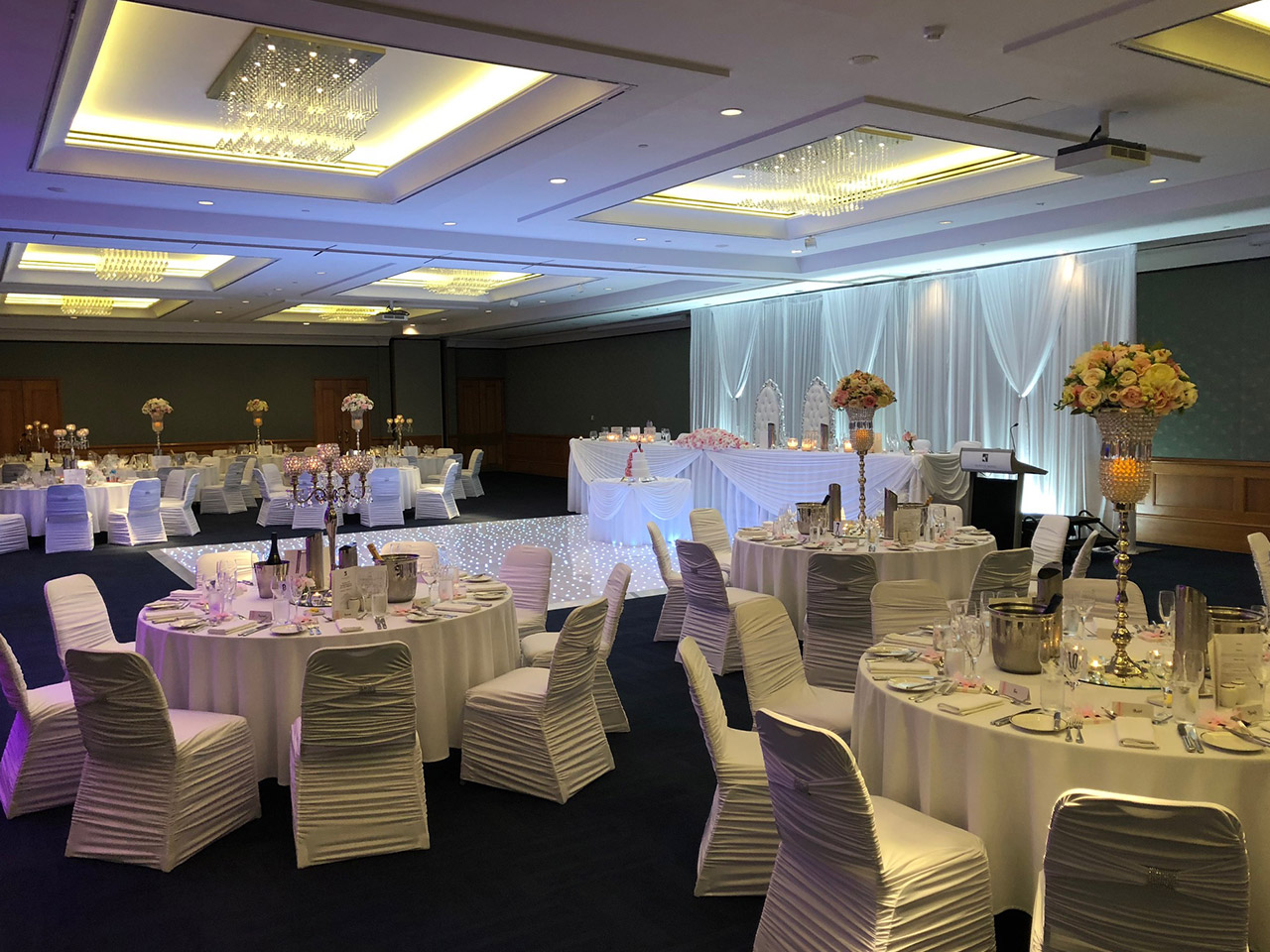 Chairs And Tables In Banquet Style, Stage Floor, Long Presidential Table And Back Drap Inside The Function Room