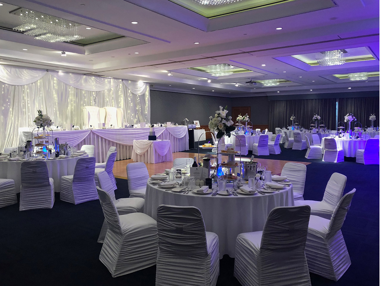 Chairs And Tables In Banquet Style With Stage Floor And A Long Presidential Table Inside The Function Room