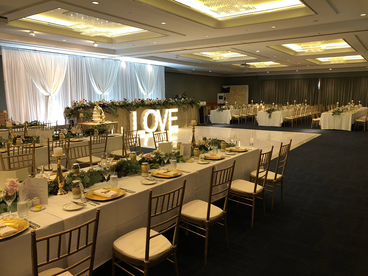 Long Tables and Chairs With Stage Back Drapping And LOVE Standee Inside The Function Room