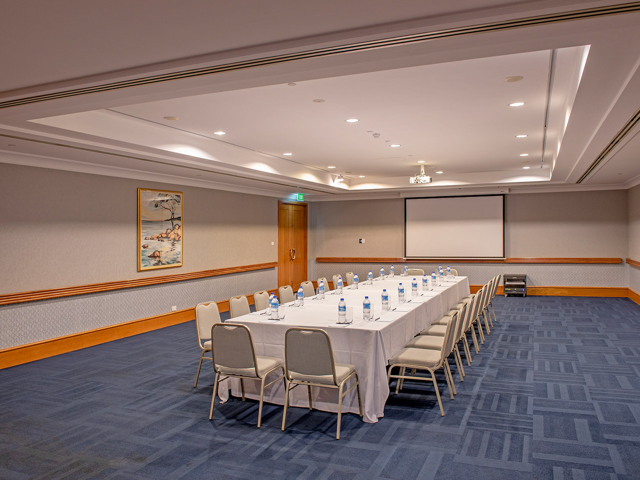 Chairs And A Long Table With Wall Painting, Bottled Water And A Projection Screen Inside The Function Room