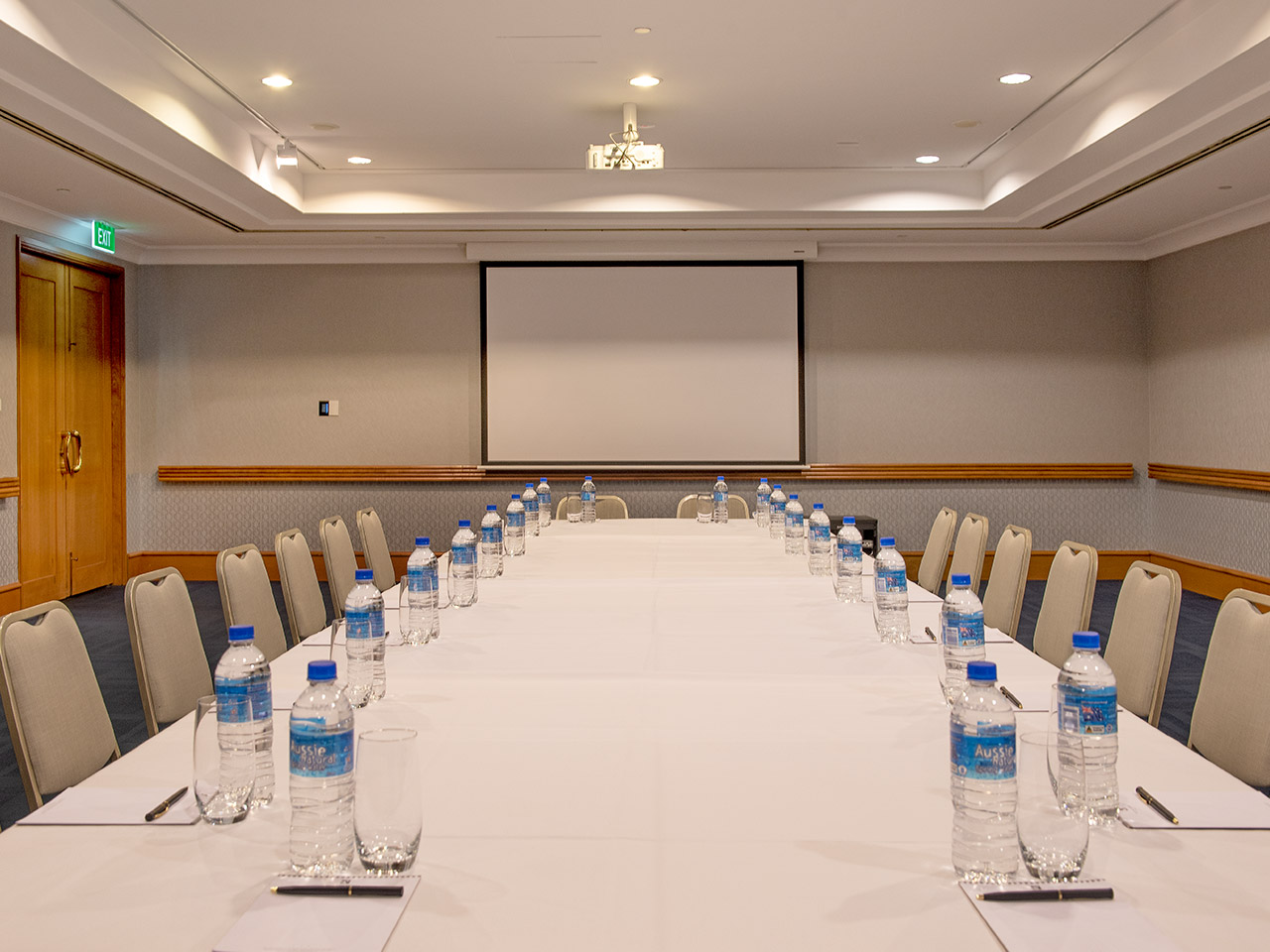 Chairs And A Long Table With Bottled Water And A Projection Screen Inside The Function Room