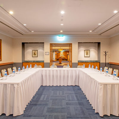Chairs And Tables In U-Shape Setup With Bottled Waters And Wall Paintings Inside The Function Room