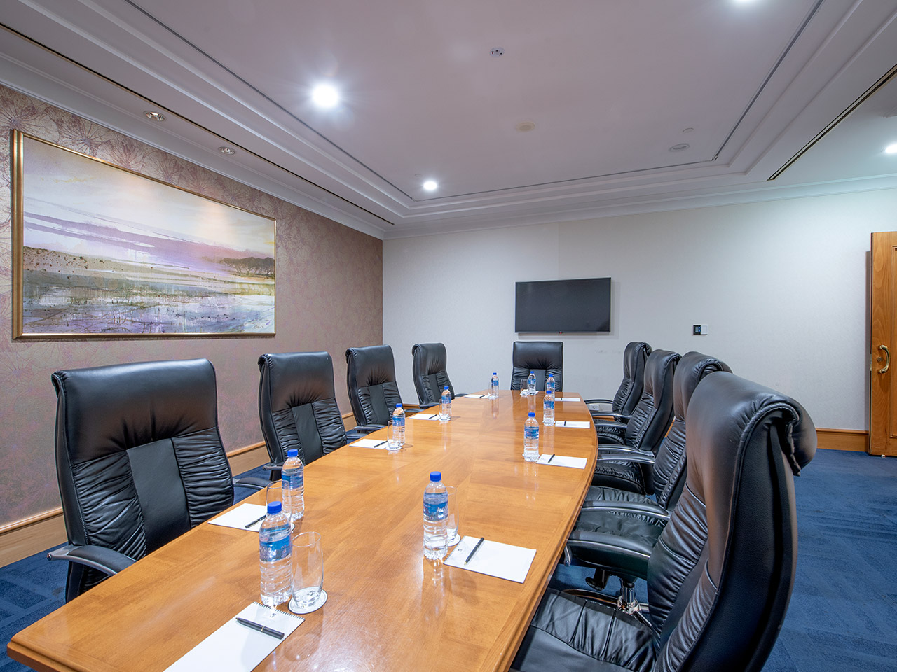Chairs And A Table With Wall Painting, TV Screen, Papers And Bottled Waters Inside The Boardroom