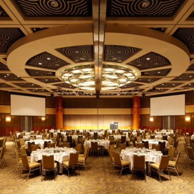 Banquet Style Setup Inside The Grand Ballroom With Projection Screens And Ceiling Lights