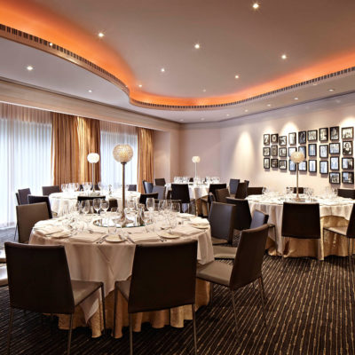 Chairs And Tables In Banquet Style With Centerpieces And Wall Picture Frames Inside The Function Room