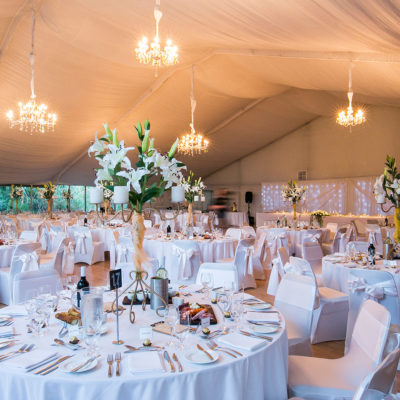 Chairs And Tables In Banquet Style Inside The Function Room With Flower Centerpieces, Chandeliers And A Special Long Table