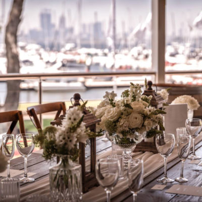 Long Dining Table Wedding Setup With River View And Flower Centerpieces