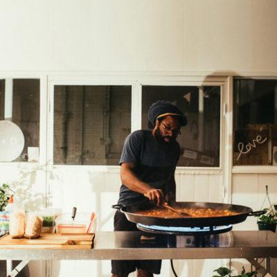 A Man Cooking Something In A Big Flat Pan