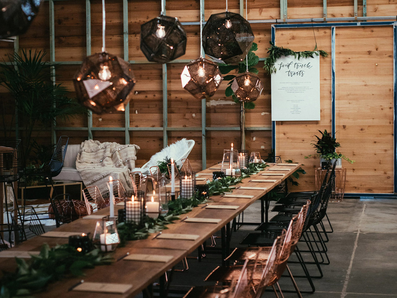 A Long Table With Chairs, Hanging Lights, Leaves And Candles