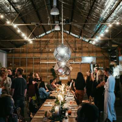 People Gathered Inside The Function Room With A Long Table And Hanging Lights