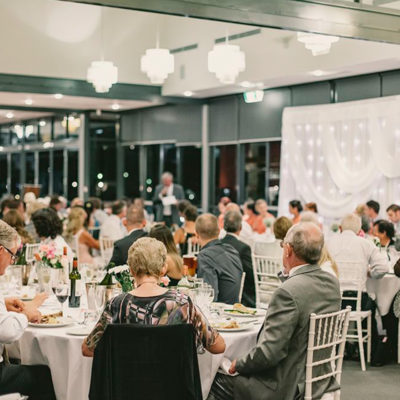 People Gathered Inside The Function Room And Seated In Banquet Style