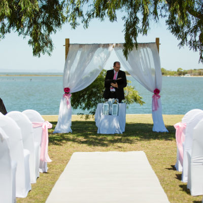Wedding Ceremony Setup Under The Trees With An Officiant Standing Under The Wood Arc And With Ocean View