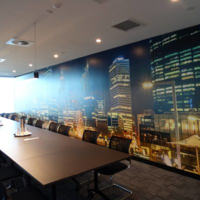 Boardroom With A Long Table And Chairs With A City Scape Image Of Perth On The Wall