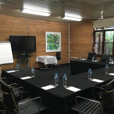 Conference Room Set Up in A U Shape With A TV Screen And Flipchart