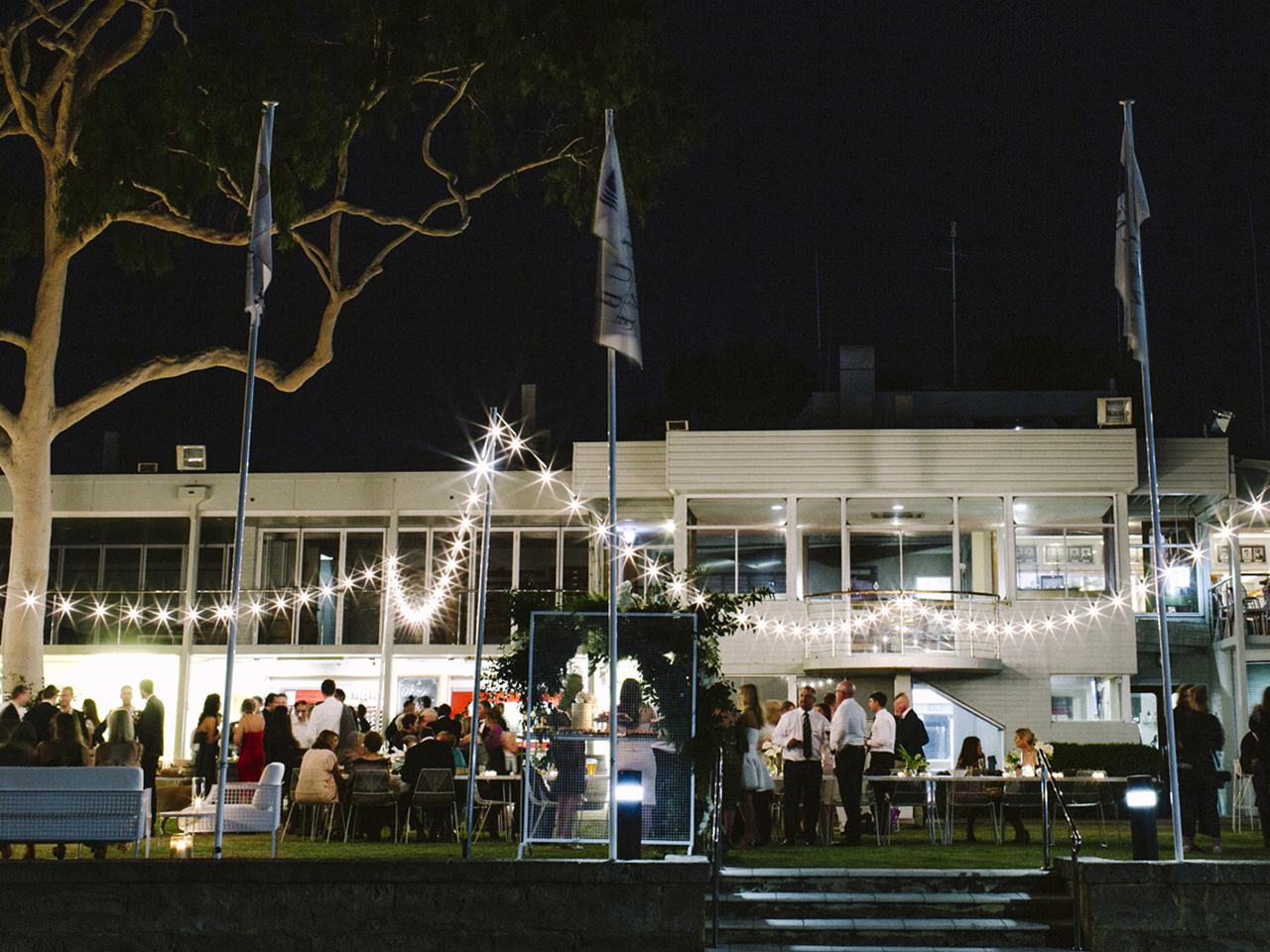 People Gathering Outside The Function Area Under A Tree With Tables, Chairs, String Lights And Flag Poles