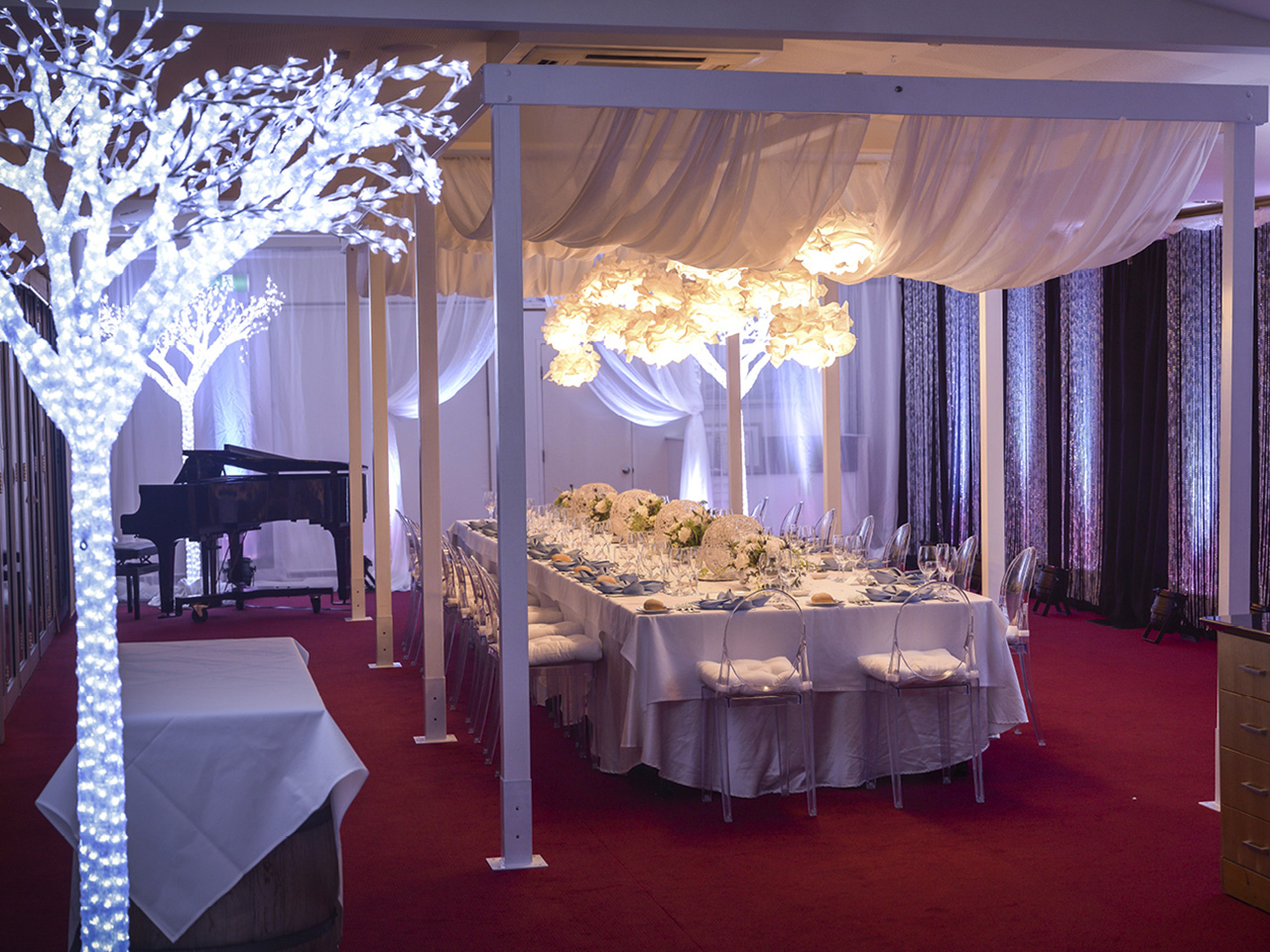 A Long Table Setup With Flower Centerpieces, Flower Chandelier, Ceiling Drapping, Piano And Artificial Tree Lights