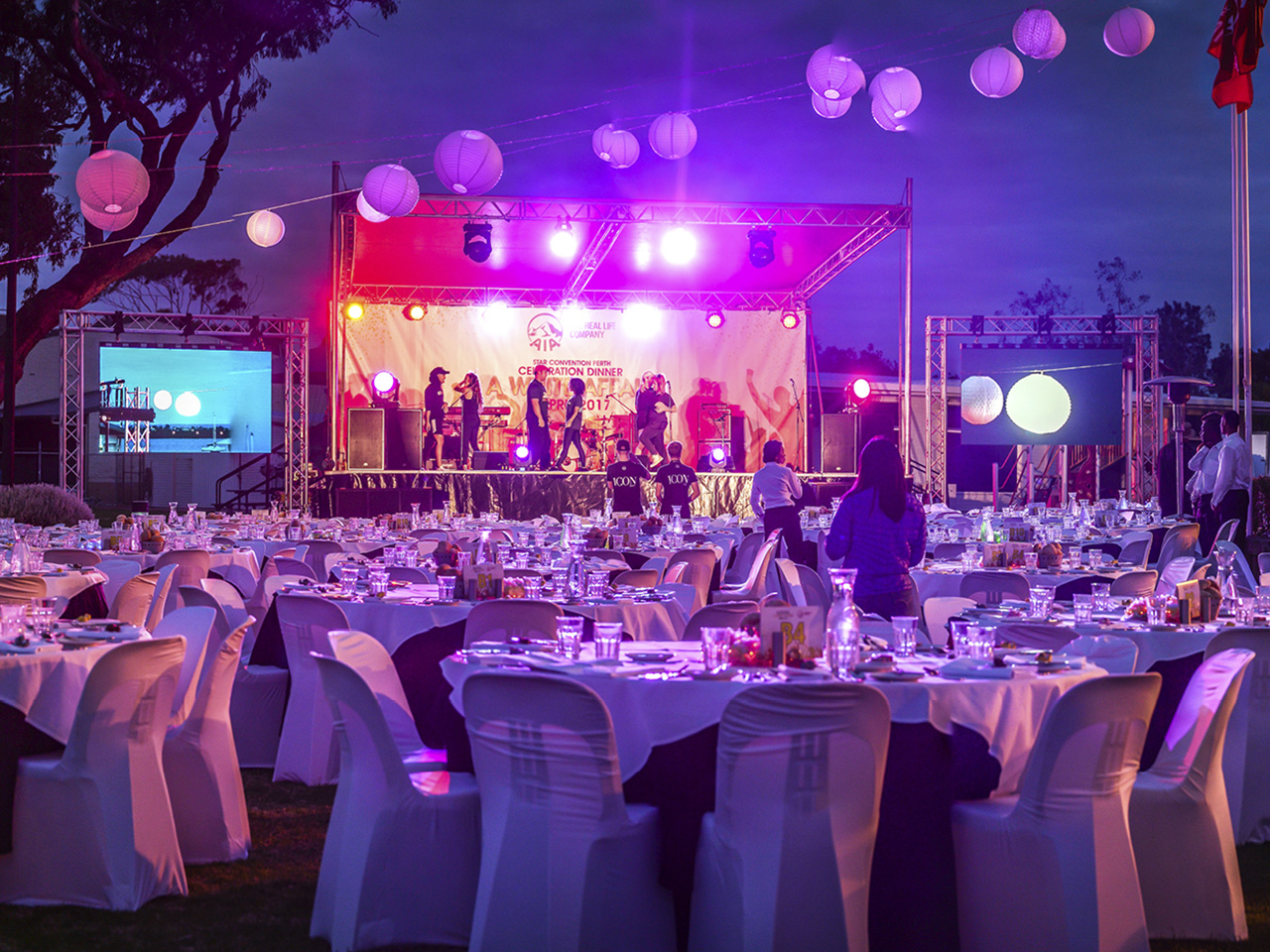 Banquet Style Open Function With Stage, Lights, Projection Screen And Performers Getting Ready