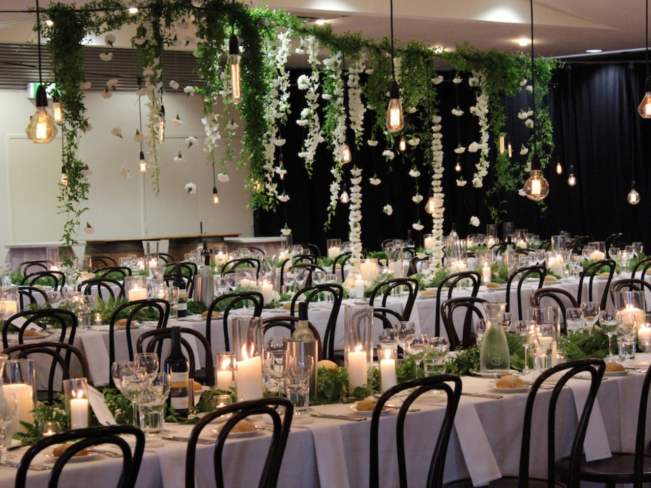 Long Tables Set Up With Candles And Table Decorations For An Event