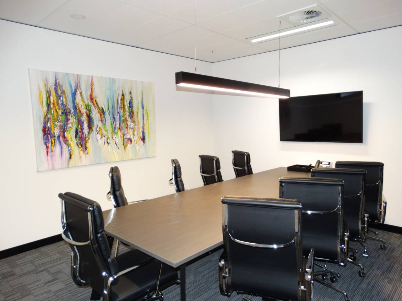 Meeting Room With A TV Screen And A Long Desk With Nine Chairs