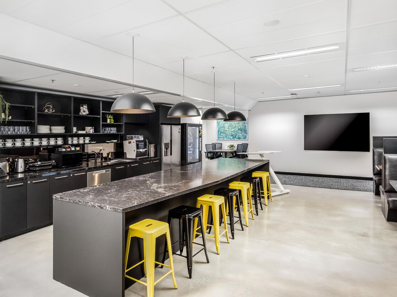 Office Kitchen With Long Table, TV Screen And Six Chairs In Black And Yellow