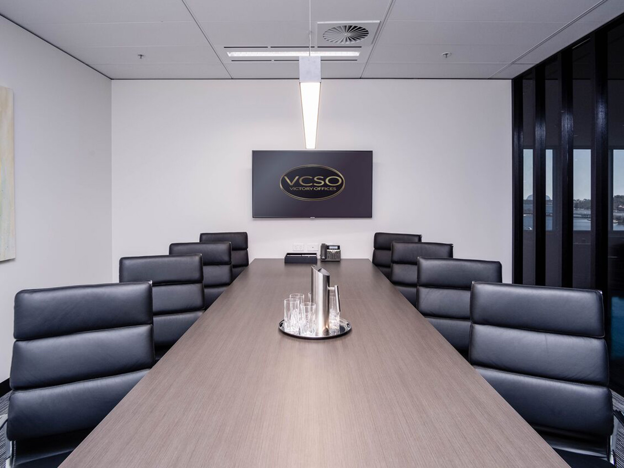 Meeting Room With A TV Screen And A Long Desk With Eight Chairs