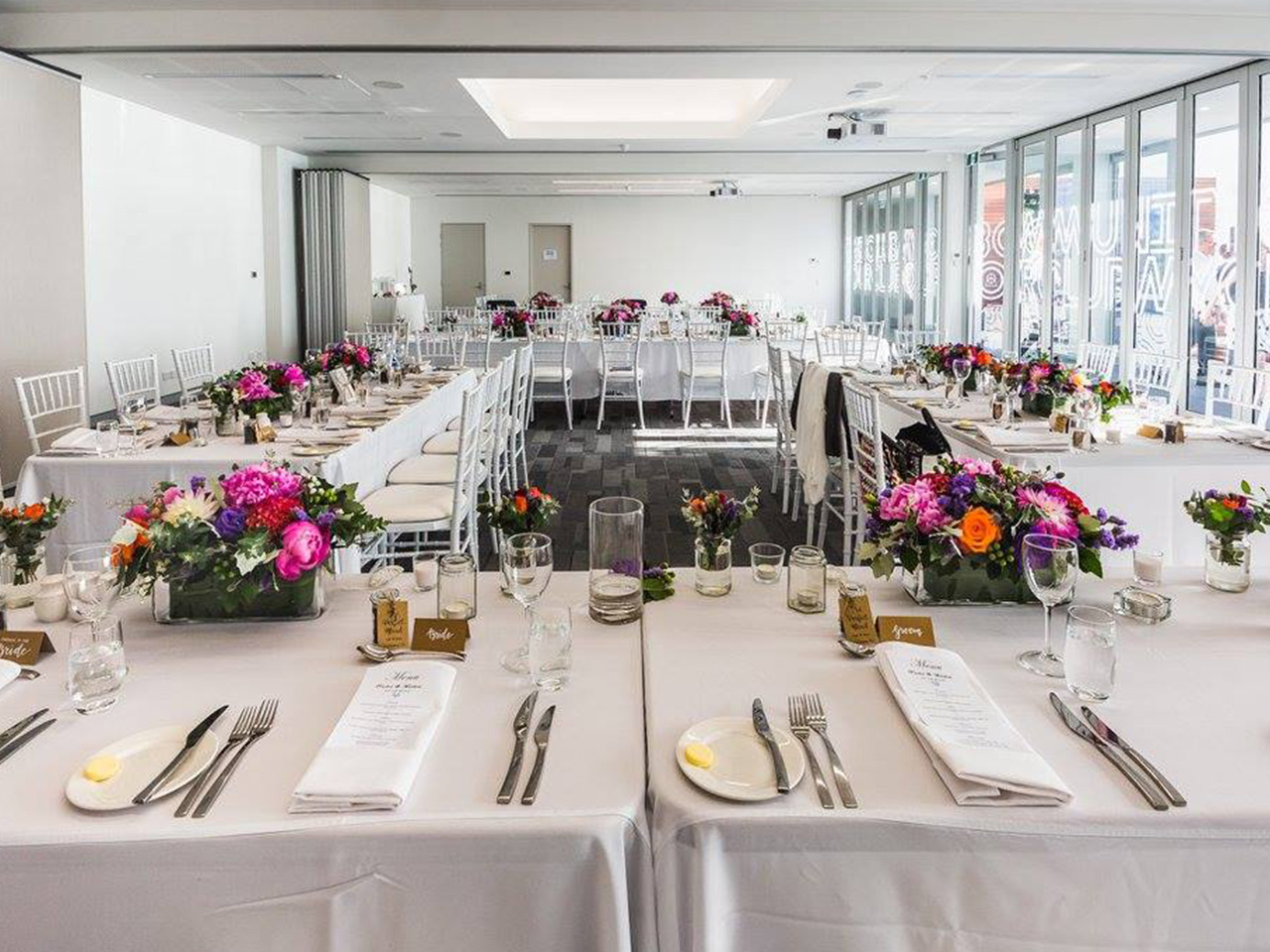 Inside The Function Room With Long Tables And Chairs And Flower Centerpieces Setup